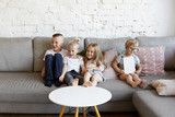 Portrait of four little friends amusing themselves sitting on comfortable sofa together and having fun, playing indoor games, feeling happy and excited. Children, friendship, joy and entertainment - 175215512