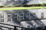 Spiegelung einer Fensterfront eines Schieferhauses/ Fassade aus Schiefer im Wasser - 175226725