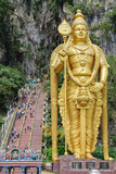 Indian tourists visit to Batu Caves in Malaysia. Main entrance with stairs and the Lord Murugan statue