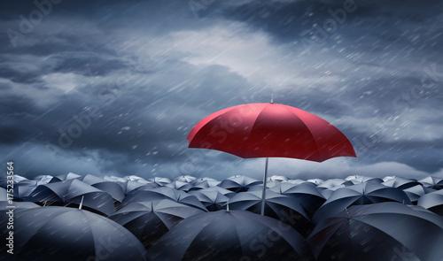 Roter Regenschirm über schwarzen Regenschirmen