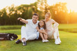 The family sits on the grass on the golf course, the man points to the side, and the wife and daughter look there