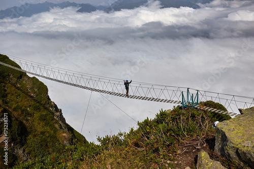 Fototapeta Man walking on suspension bridge and looking at cloudy mountains below.