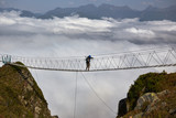Man walking on suspension bridge and looking at cloudy mountains below. - 175238794