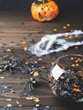 Halloween orange and black confetti with spiders and spider net on dark rustic wooden background. Holiday decoration symbols