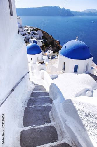 Fotobehang Santorini Santorini Island, the city of Oia, Greece. Traditional Greek architecture, white houses and churches with blue domes above Caldera, Aegean Sea.