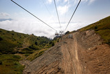 View from top of ropeway with multiple seats and stretched cables above trees in deep fog. Mountains of the North Caucasus. - 175240943