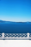 Traditional Greek architecture and a view of the blue sea over a white terrace. Santorini, Cyclades, Greece. - 175242340