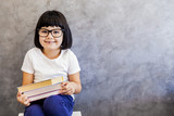Black hair little girl with glasses holding books by the wall - 175243524