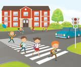 School children cross road on pedestrian crossing, near school building