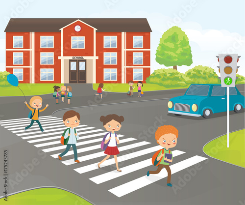 School children cross road on pedestrian crossing, near school building - 175245785