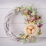 Decorative woven wreath is decorated with flowers and quail eggs. - 175250972