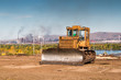 Yellow bulldozer against the backdrop of an industrial landscape
