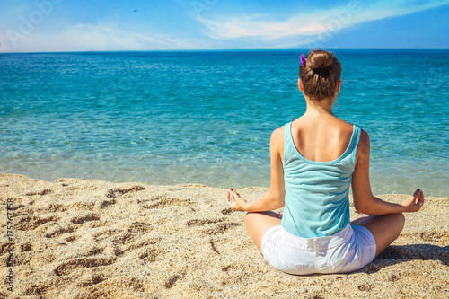 Deurstickers School de yoga Young woman meditates on the beach
