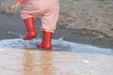 wellingtons in puddle.kid rubber boots in the sea background - 175272799