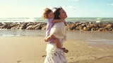 Little girl piggyback on mother singing happy in front of ocean slow motion - 175283195