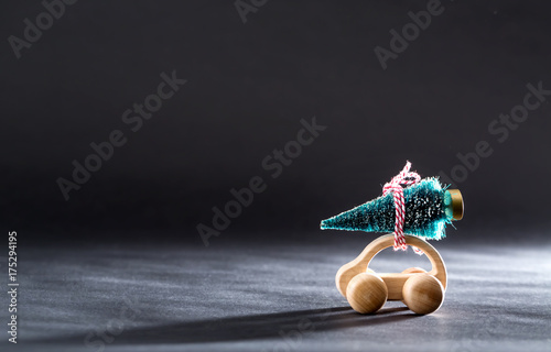 Plakat Miniature wooden car carrying a Christmas tree on a black backdrop