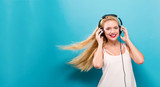 Happy young woman with headphones on a solid background - 175294762