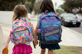 Two girls are walking to school holding hands on their first day wearing backpacks. - 175307386