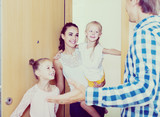 Adults and kids meeting at doorway and greeting one another - 175312327