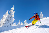 Skier skiing downhill in high mountains against blue sky - 175319577