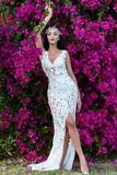 Girl posing on violet floral background - 175320358