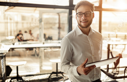 Businessman holding mobile device in cafe