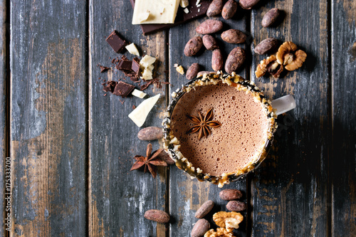 Foto op Canvas Chocolade Vintage mug of hot chocolate, decor with nuts, caramel, spices. Ingredients above. Chopped dark and white chocolate, cocoa beans, anise over old wooden table. Top view with space. Dark rustic style
