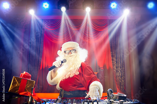 Funny Santa DJ mixes in the beams of light music for Christmas. Poster