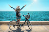 Blonde woman in summer hat with her bicycle walking coastline by - 175337190