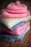 Pile of soft mohair hand knit clothes in pink, blue and white - 175339904