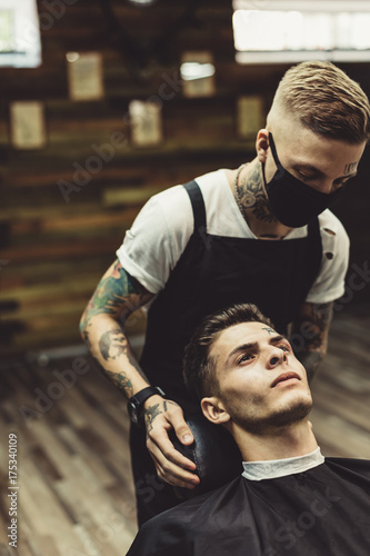 Crop stylist preparing young tattooed man in chair for shaving in barbershop Plakat