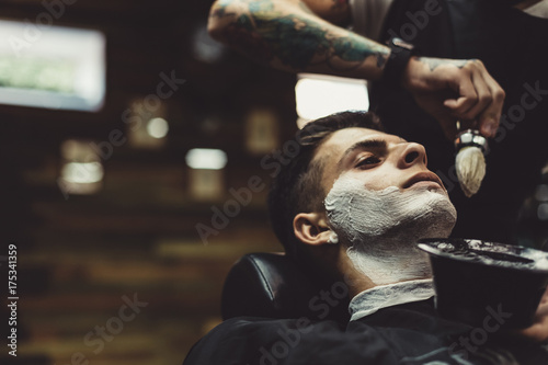 Crop stylish applying foam on customer's cheeks for shaving while working in barbershop. © kkolosov