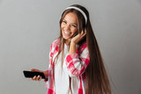Close-up portrait of young laughing pretty woman in headphones listening to music