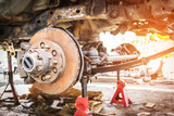 Old and rusty car's suspension, which removes the wheels for repair, replacement and change news parts -Automotive industry and garage concepts. - 175360909
