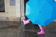 Person with pink boots and blue umbrella splashing in the puddle