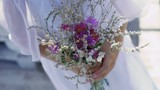The bouquet of wildflowers in the hands of young girl. Slowly - 175363704
