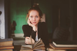 indoor portrait of redhead happy woman learning or reading books in university or library - 175365381