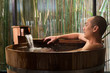 Onsen series: Asian man taking a bath in wooden bathtub