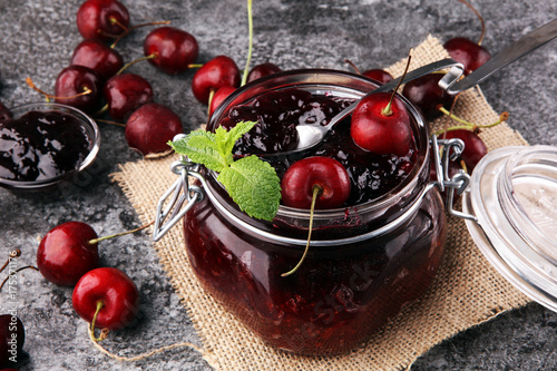 Fotobehang Kersen Jar of cherry jam, sour cherries and spoon on grey vintage background