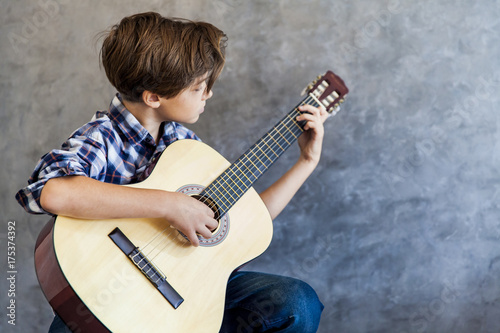 Cute teenage boy playing acustic guitar Poster