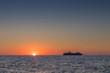 Beautiful sunset in Oia, Santorini. With silhouette of luxury cruise.