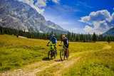 Mountain biking couple with bikes on track, Cortina d'Ampezzo, Dolomites, Italy - 175386738