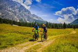 Mountain biking couple with bikes on track, Cortina d'Ampezzo, Dolomites, Italy - 175386738