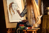 Artist painting on easel in studio. Girl paints portrait of woman with brush. Female painter seen from behind. Indoor home interior for handmade crafts. Student works as an artist. - 175389506