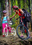Bikes cycling family. Happy mother and daughter wearing helmet are cycling on bicycles into forest. Parenting. Children travel unaccompanied.
