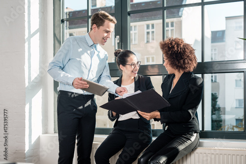 Fridge magnet Three young cheerful employees smiling while holding a tablet PC and a folder during break in a modern office