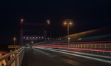 Autos und Bahn auf nächtlicher Brücke - 175397185