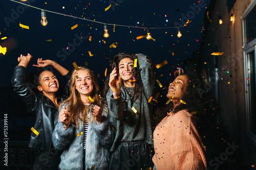 Night party on a terrace. Happy women having fun under confetti.