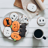 Preparation for Halloween. Coffee and scary gingerbread cookies on a wooden background. - 175400707