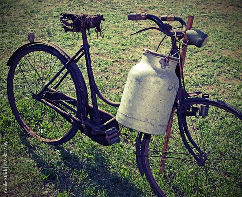 Staande foto Fiets ancient milking bike with milk bin and vintage effect
